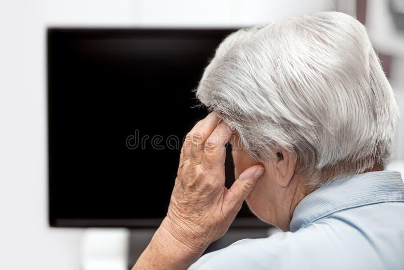 Äldre kvinna med huvudvärken som framme sitter av ett skrivbord eller en tv, Co arkivbilder