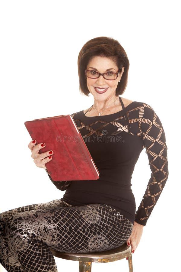 Äldre kvinna med minnestavlablickleende arkivfoton