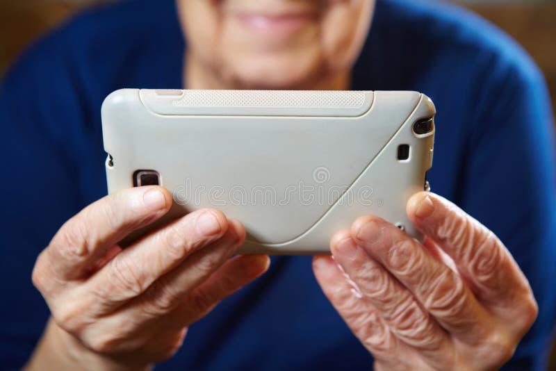 Äldre kvinna med minnestavladatoren arkivfoto