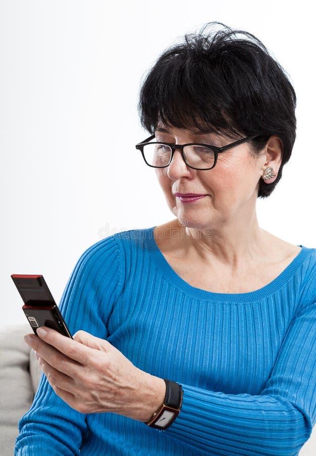 Äldre kvinna med mobiltelefonen royaltyfria bilder