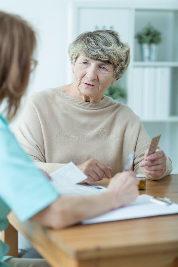 Äldre kvinna med socialarbetaren arkivbilder