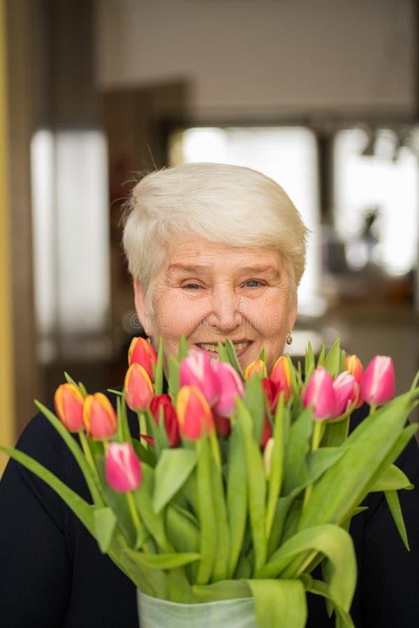 Äldre kvinna med tulpanblommor arkivbilder