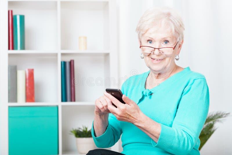 Äldre kvinna och smartphone arkivbilder