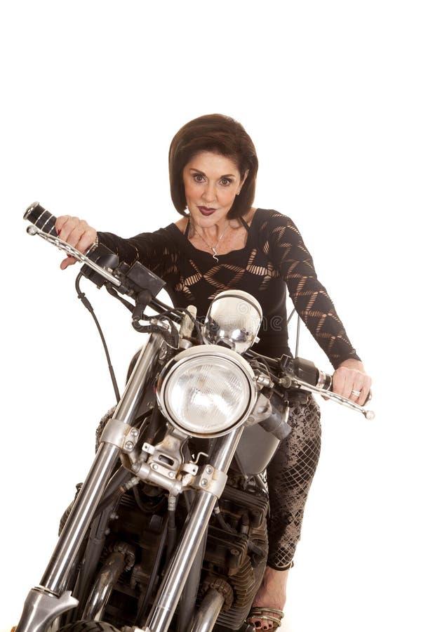 Äldre kvinna på den allvarliga motorcykeln royaltyfri fotografi