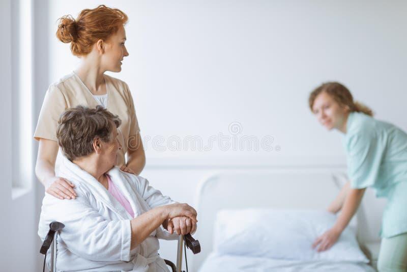 Äldre kvinna på rullstolen i vårdhem med den hjälpsamma doktorn på hennes sida och unga sjuksköterska som gör sängen royaltyfria foton