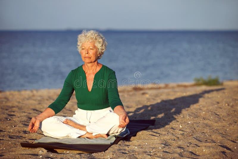Äldre kvinna på stranden som mediterar vid havet royaltyfria bilder