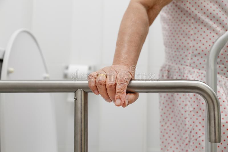 Äldre kvinna som är hållande på ledstången i toalett royaltyfria bilder