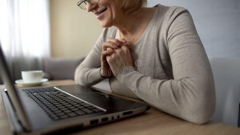 Äldre kvinna som är lycklig att se hennes barn i internet som ser bärbar datorskärmen arkivfoto
