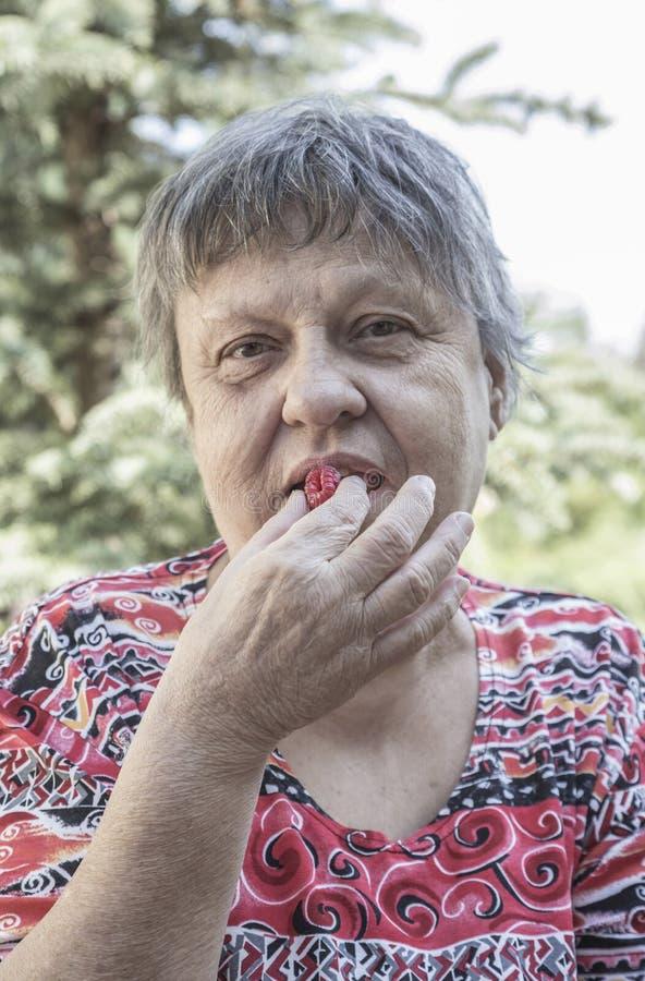 Äldre kvinna som äter en bärfrukt arkivfoto