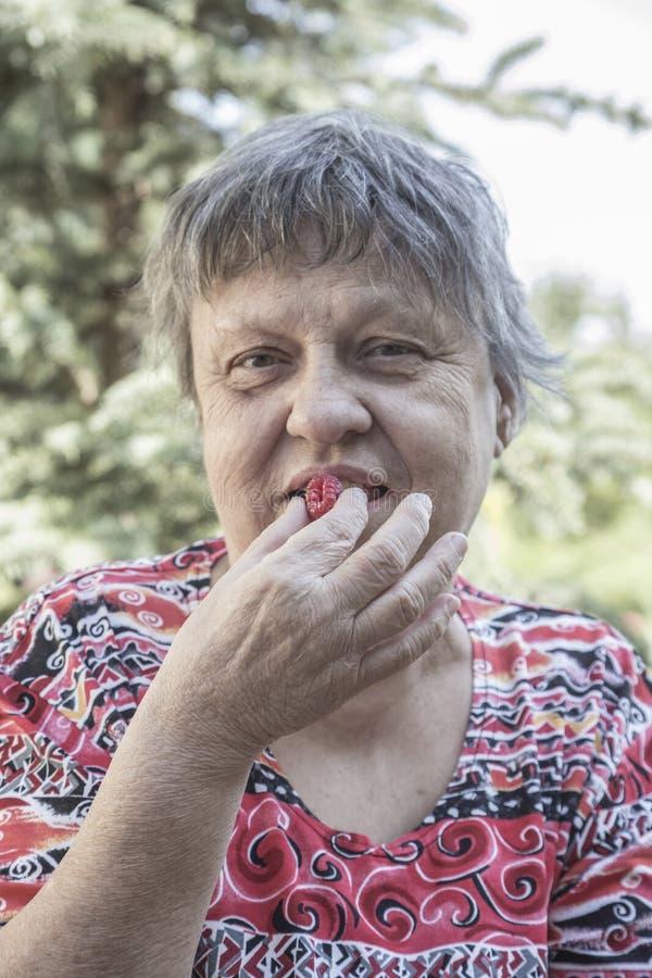 Äldre kvinna som äter en bärfrukt royaltyfri fotografi
