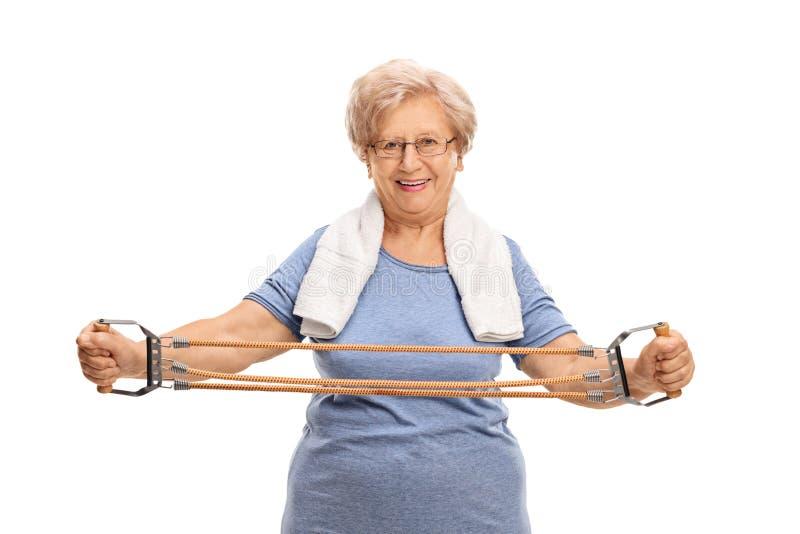 Äldre kvinna som övar med motståndsmusikbandet fotografering för bildbyråer