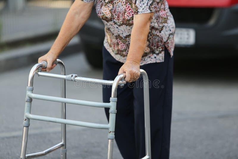 Äldre kvinna som använder en metallfotgängare arkivbilder