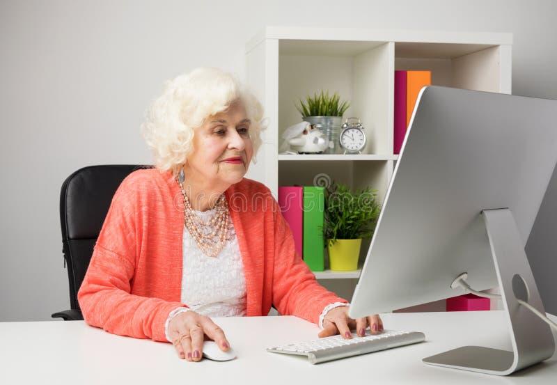 Äldre kvinna som arbetar i kontoret fotografering för bildbyråer
