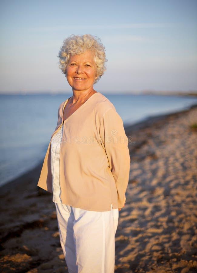 Äldre kvinna som bara står på stranden royaltyfri foto