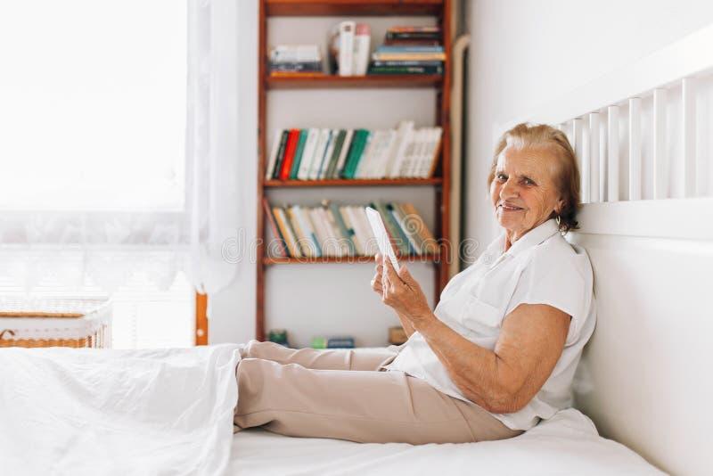 Äldre kvinna som bekvämt sitter på säng och använder hennes minnestavla royaltyfria foton