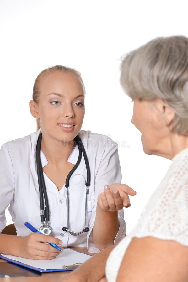 Äldre kvinna som besöker doktorn arkivfoton