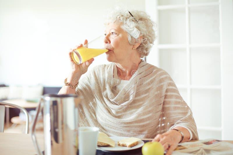 Äldre kvinna som dricker fruktsaft arkivbilder