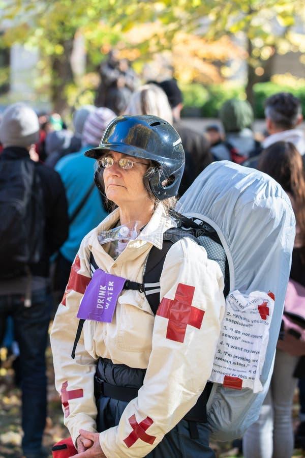 Äldre kvinna som en gataläkare under politisk protest royaltyfri bild