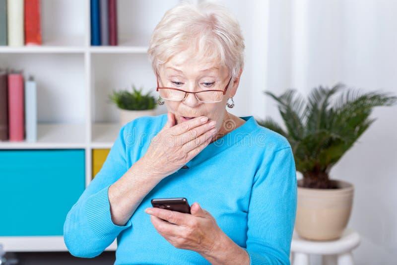 Äldre kvinna som förvånas av textmeddelandet royaltyfria foton