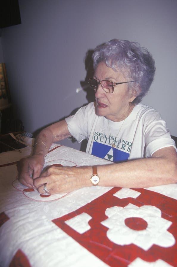 Äldre kvinna som gör ett täcke, Beaufort, SC arkivbild