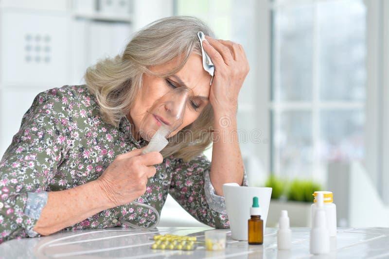 Äldre kvinna som gör inandning royaltyfri foto