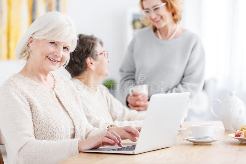 Äldre kvinna som gör online-shopping arkivfoton