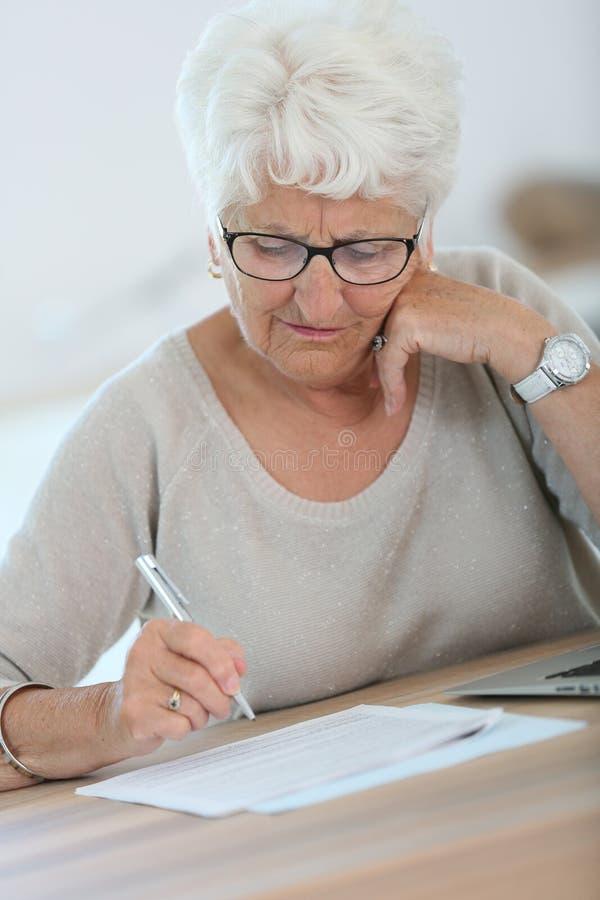 Äldre kvinna som gör skrivbordsarbete med bärbara datorn royaltyfri bild