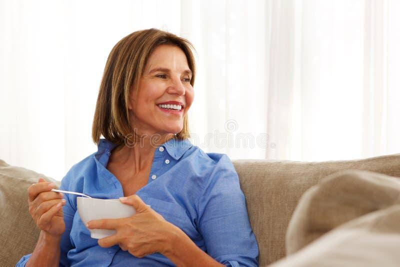 Äldre kvinna som hemma sitter med bunken av frukosten arkivfoton