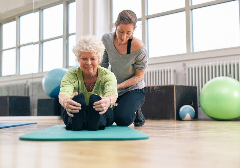 Äldre kvinna som hjälps av hennes instruktör i idrottshallen royaltyfri foto