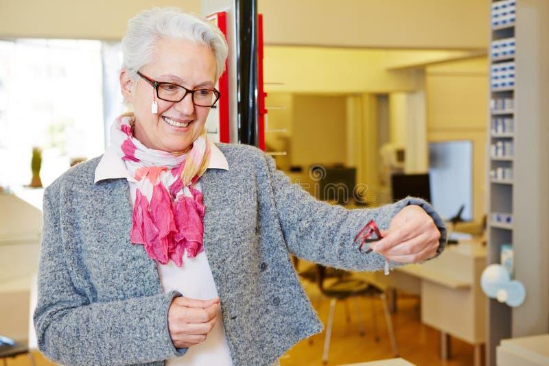 Äldre kvinna som jämför exponeringsglas royaltyfri foto