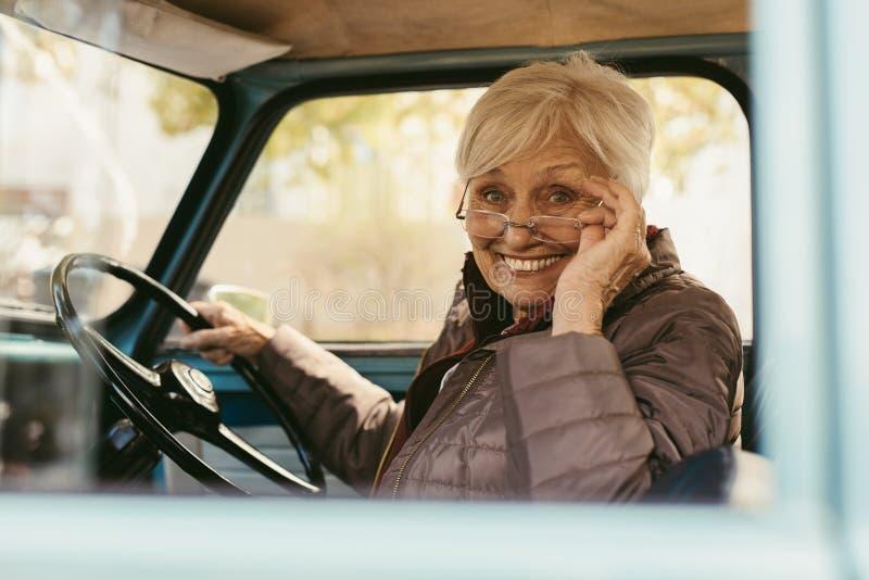 Äldre kvinna som kör en gammal bil arkivbild