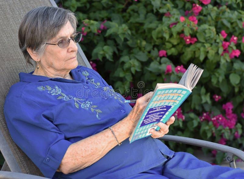 Äldre kvinna som läser en bok på henne hem- trädgård royaltyfri bild