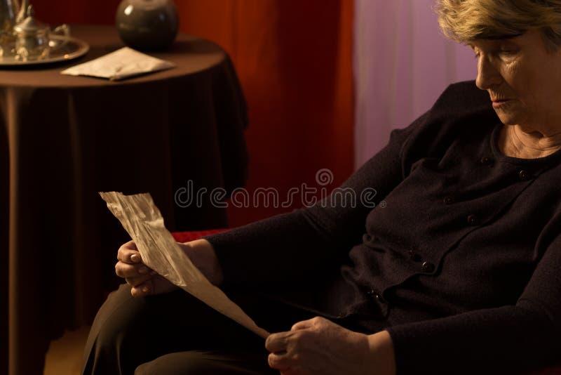 Äldre kvinna som läser ett brev royaltyfri fotografi