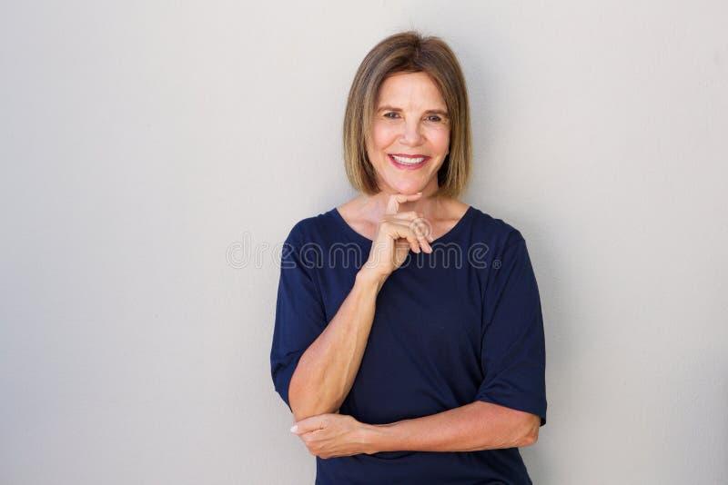Äldre kvinna som ler med handen till hakan royaltyfria foton