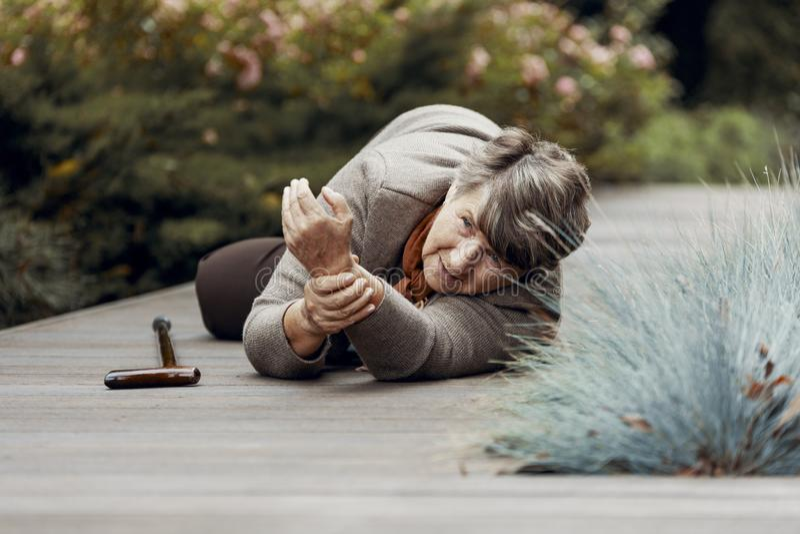 äldre kvinna som ligger på golvet och den väntande på hjälpen efter hjärtinfarkt royaltyfri bild