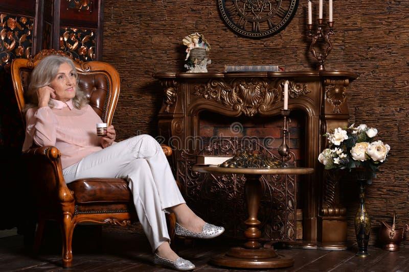Äldre kvinna som poserar i rum arkivbild