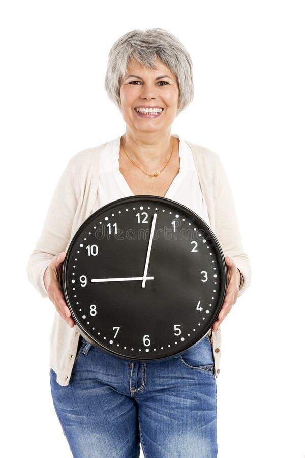 Äldre kvinna som rymmer en klocka royaltyfri bild