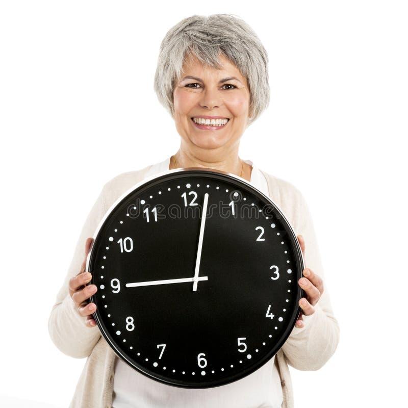 Äldre kvinna som rymmer en klocka arkivfoton
