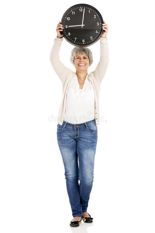 Äldre kvinna som rymmer en klocka arkivfoto