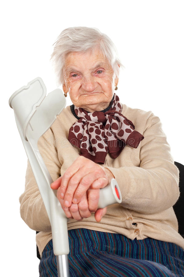 Äldre kvinna som rymmer hennes krycka arkivbilder