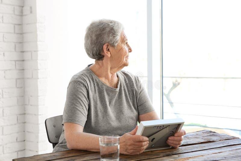 Äldre kvinna som rymmer träramen och ut ser fönstret royaltyfria foton