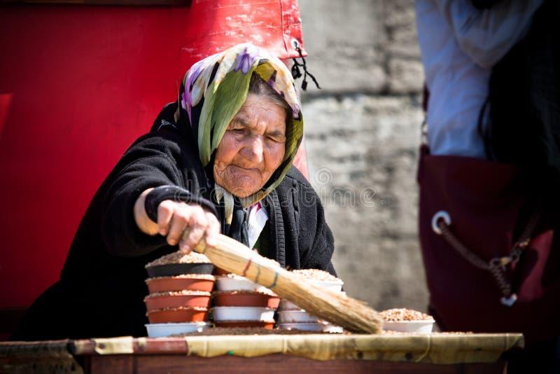 Äldre kvinna som säljer fågelfrö arkivfoton