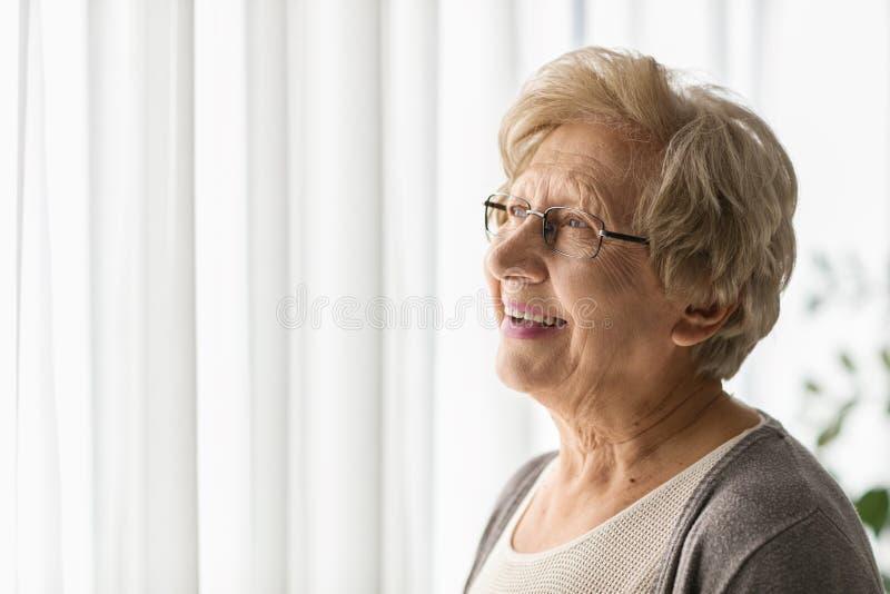 Äldre kvinna som ser till och med ett fönster royaltyfria bilder