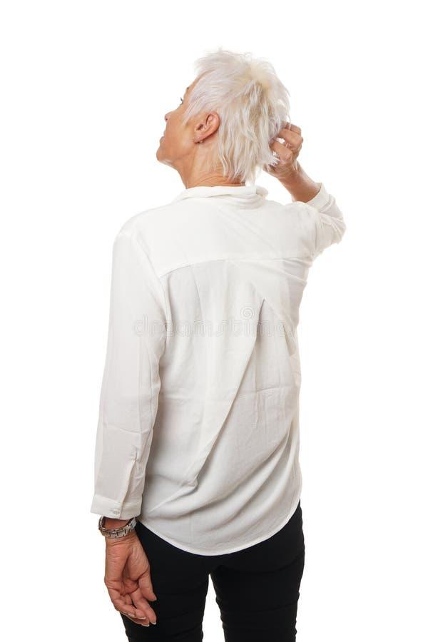 Äldre kvinna som skrapar hennes huvud royaltyfri bild