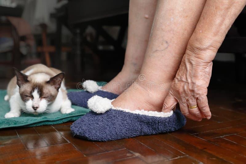 Äldre kvinna som svällas fot som sätter på skor royaltyfria foton
