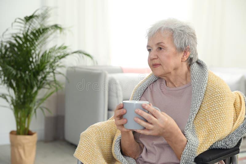 Äldre kvinna som täckas med filten som dricker te på vårdhemmet Hjälpa högt folk royaltyfria foton