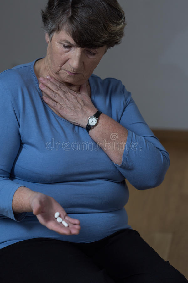 Äldre kvinna som tar medicin arkivfoton