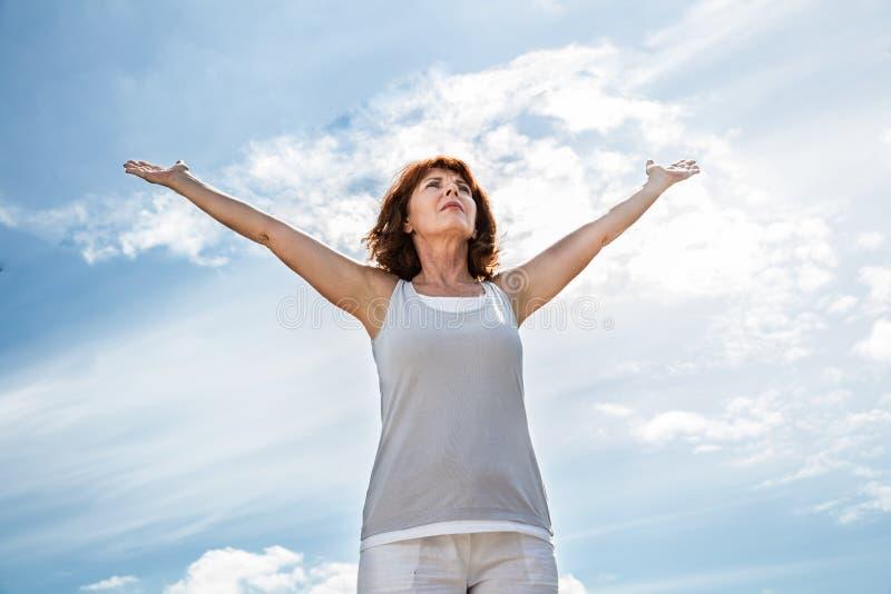 Äldre kvinna som upp öppnar hennes armar för att öva yoga utomhus royaltyfri foto