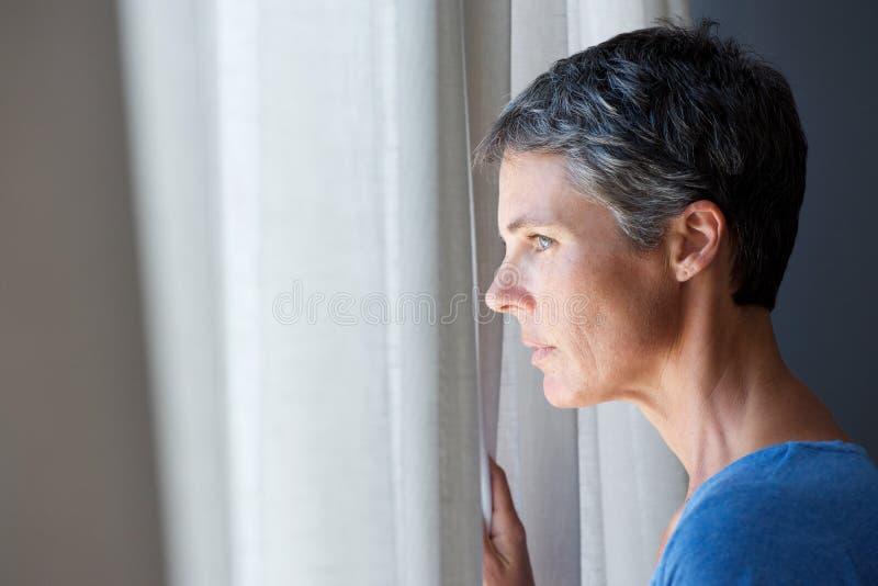 Äldre kvinna som ut ser fönstret royaltyfria bilder