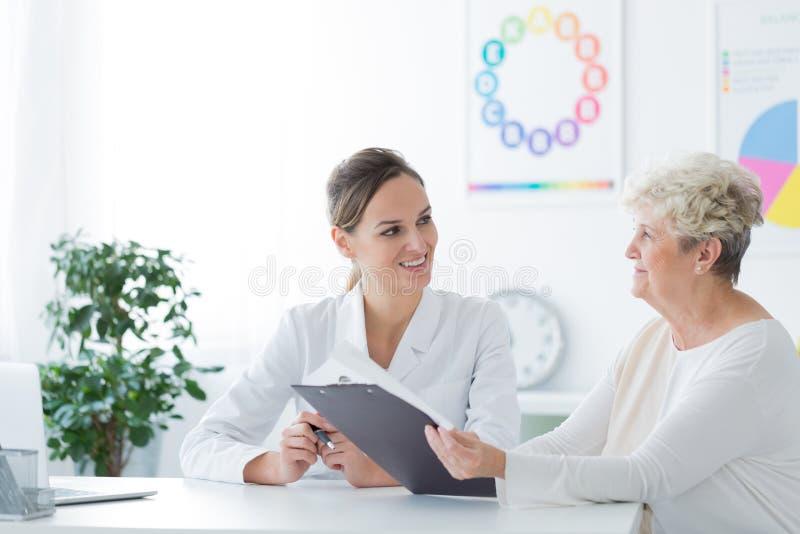 Äldre kvinna under dietistkonsultation arkivfoto